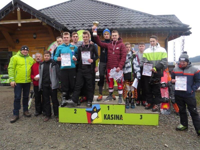 Zwycięzcy mistrzostw stojący na podium, obok opiekunowie