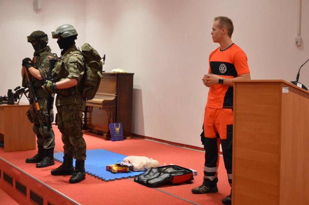 dwóch uzbrojonych wojskowych i ratownik medyczny udziela instrukcji udzielania pierwszej pomocy