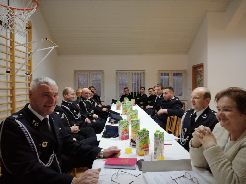 Członkowie OSP siedzący przy stole podczas zebrania