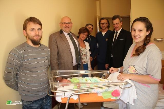 Starosta , wicestarosta, lekarze i rodzice stoją koło noworodka
