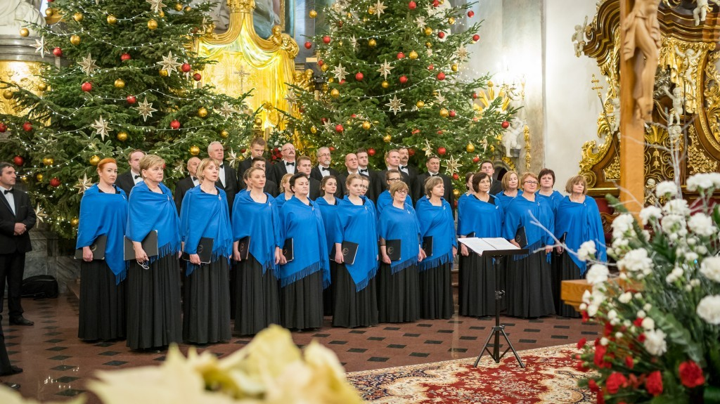 Zdjęcie grupowe członkow chóru, w tle ołtarz i choinki