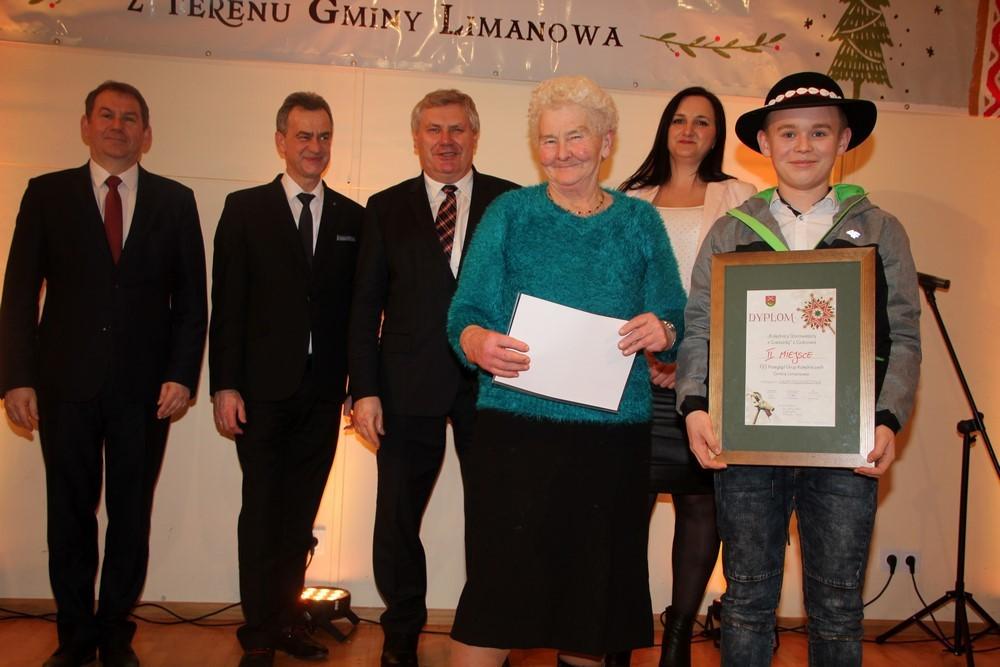 chlopiec w przebraniu pastuszka trzyma dyplom , obok przedstawiciele samorządów gminy Limanowa i Powiatu Limanowskiego