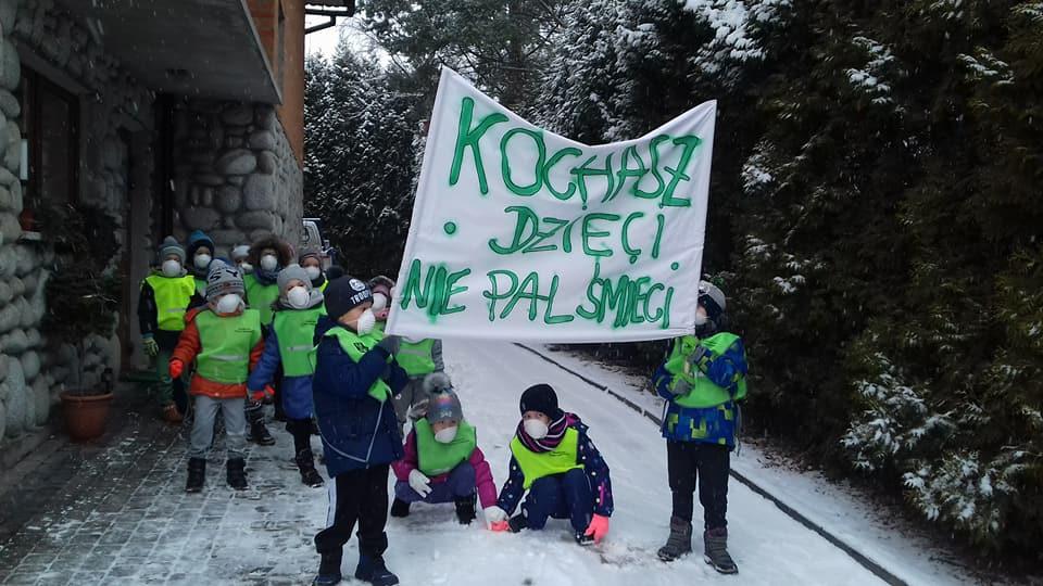 Dzieci trzymające transparent z napisem: Kochasz dzieci - nie pal śmieci