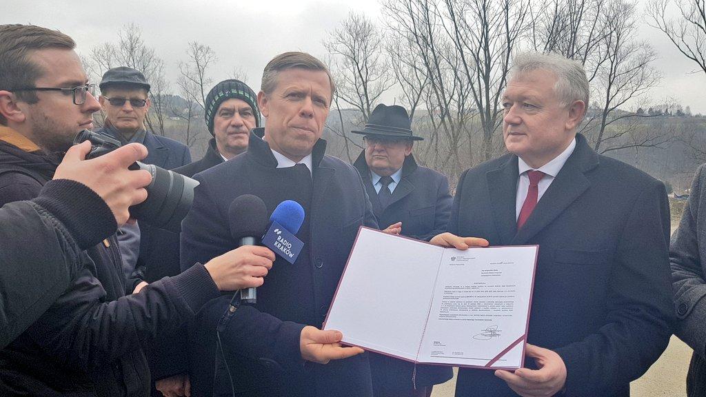 Wojewoda Małopolski Piotr Ćwik trzymający promesę dla miasta Liamnowa