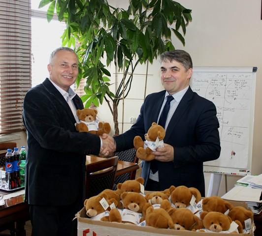 Pan mieczysław Joniec przekazuje misie ratownisie na ręce dyrektora limanowskiego szpitala