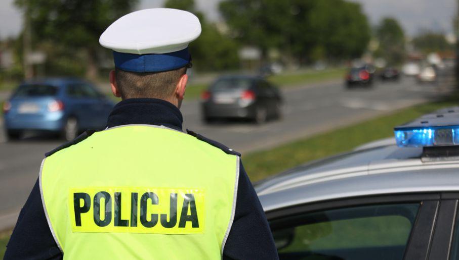 policjant na tle jadących samochodów