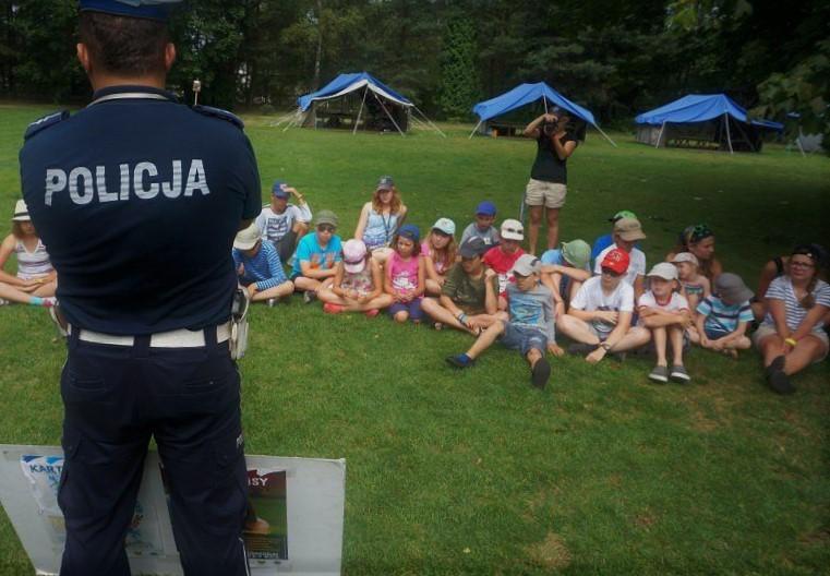 Policjant tłumaczy dzieciom zasady bezpieczneństwa podczas wakacji 2018