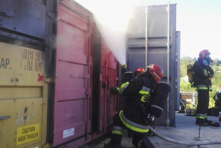 Zdjęcie ze szkolenia z zakresu gaszenia pożarów wewnętrznych - na zdjęciu strażacy gaszą ogień w magazynie