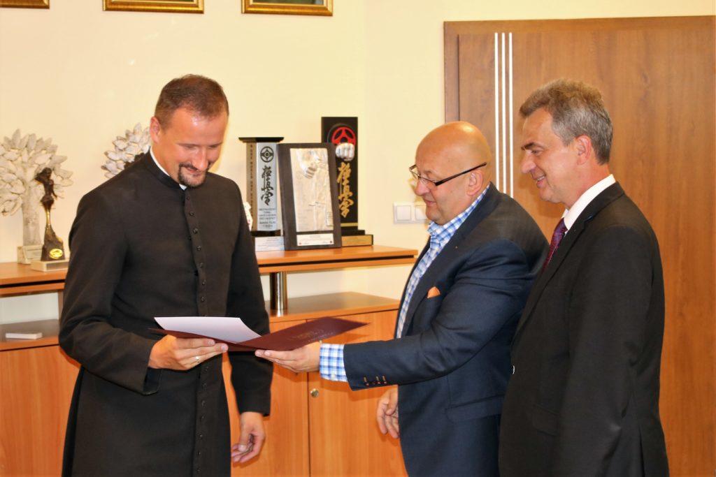 Starosta i Wicestarosta wręczają list gratulacyjny dla ksiedza