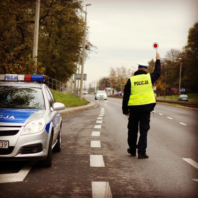 policjant w żółtej kamizelce podczas kontroli drogowej
