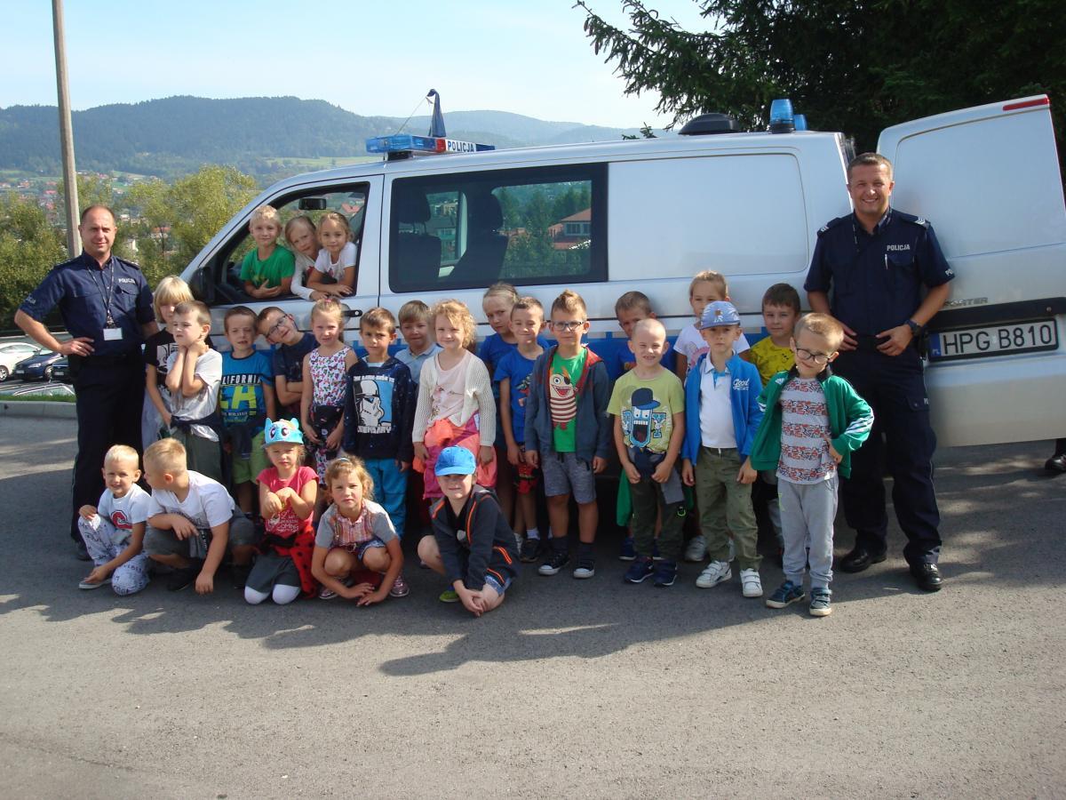 Dzieci z wizytą w komendzie powiatowej - zdjecie dzieci z policjantami przy samochodzie