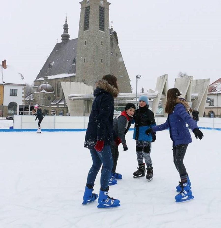 dzieci jeżdżące na łyżwach na lodowisku w limanowej. W tle bazylika