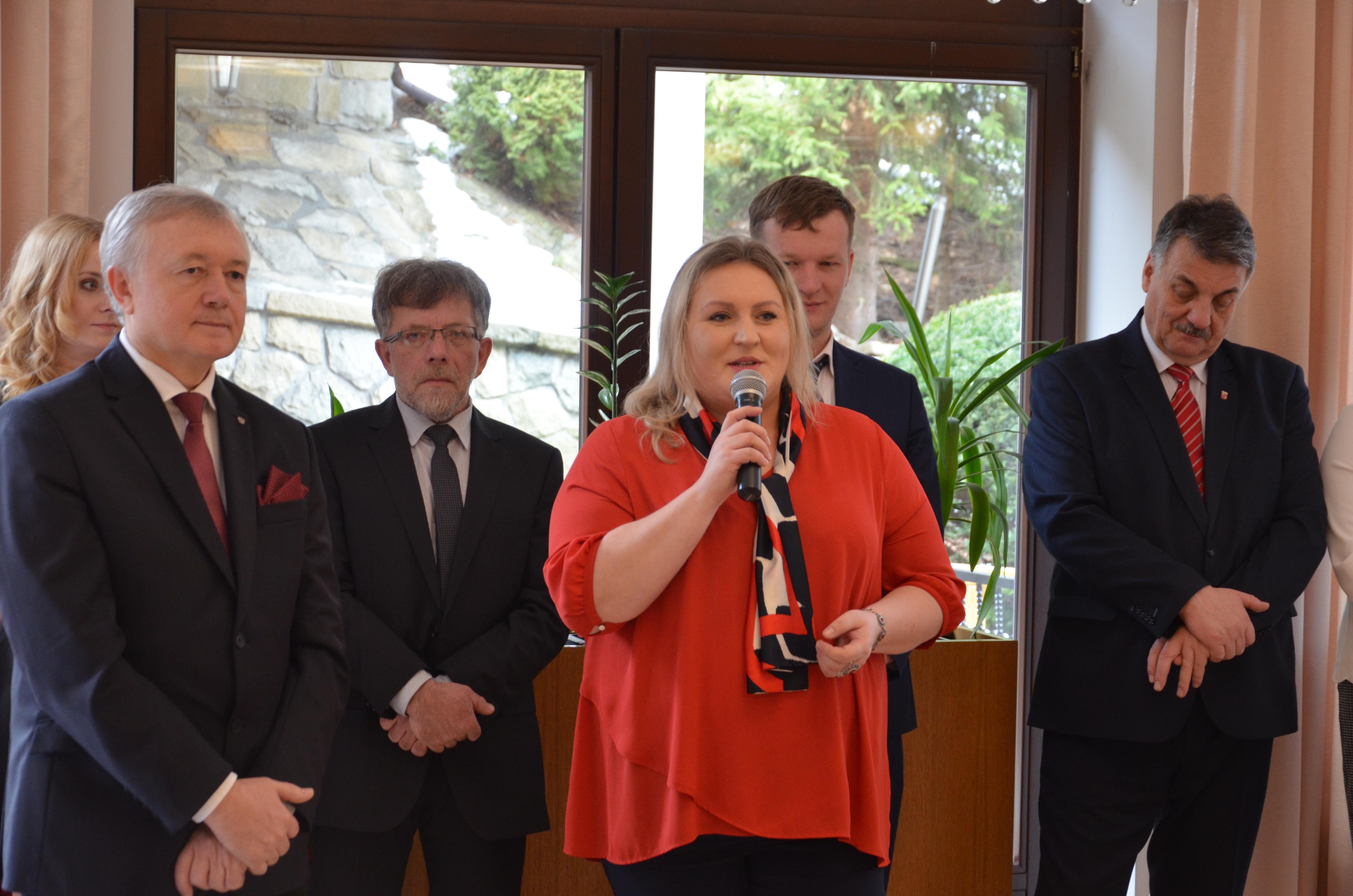 Przewodnicząca Rady Powiatu Limanowskiego Ewa Filipiak składa jubilatom życzenia. W tle Poseł W. Janczyk oraz przedstawiciele gminy i miasta mszana dolna.
