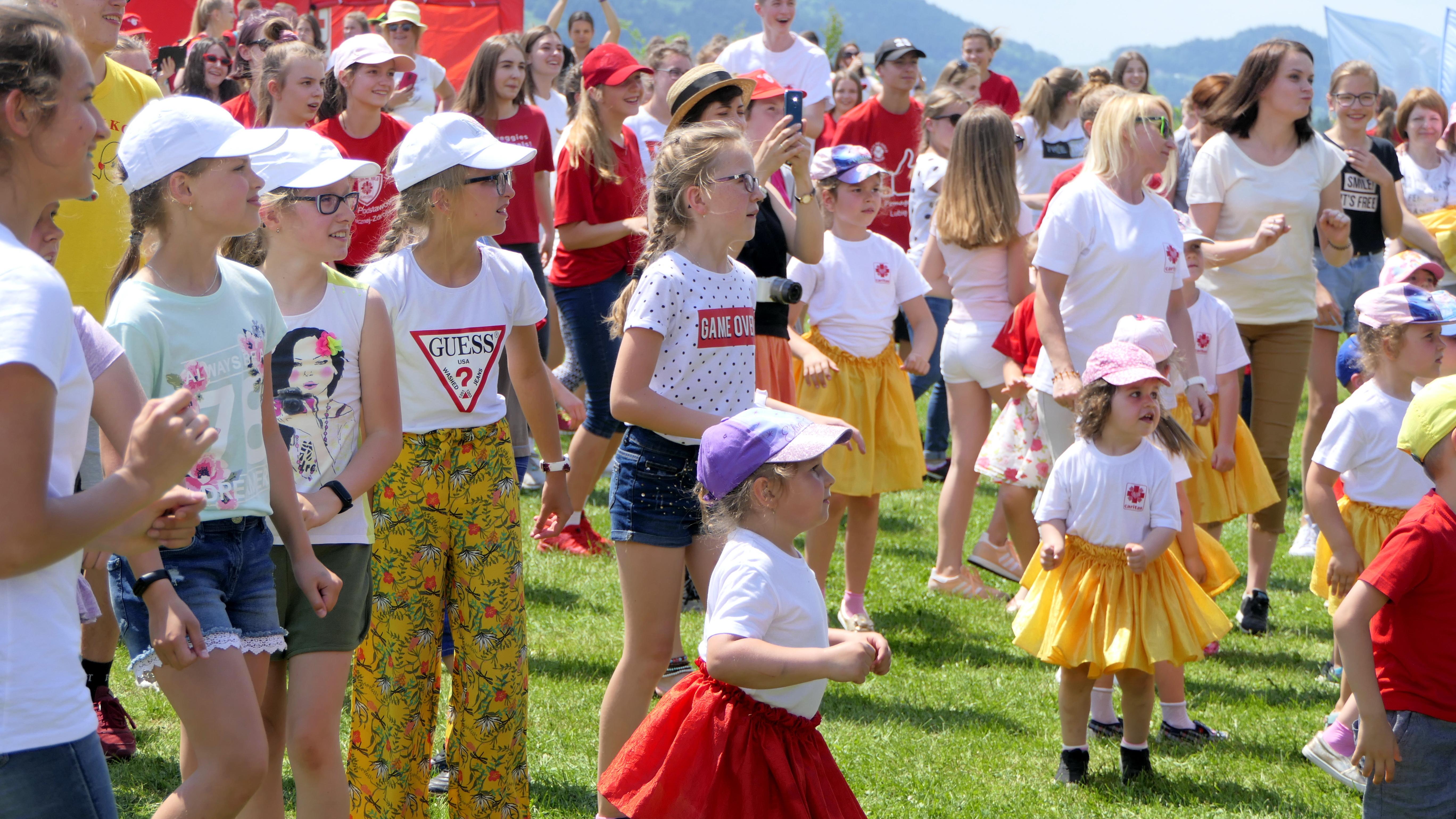 uczestnicy zjazdu szkolnych kół caritas bawiący się i tańczący na łące