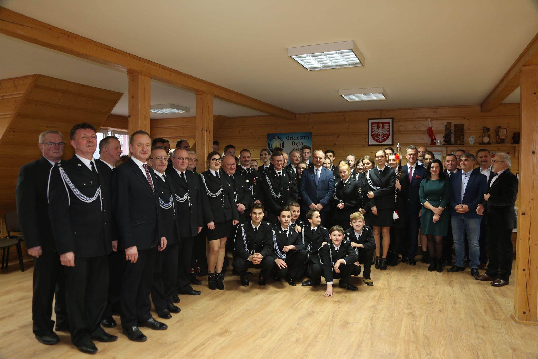 Koncert Jubileuszowy Orkiestry Dętej przy OSP w Męcinie - członkowie zespołu na wspólnym zdjęciu