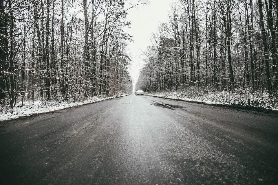 grafika przedstawiająca pojazd na drodze zimą - osrzeżenie przed gołoledzią