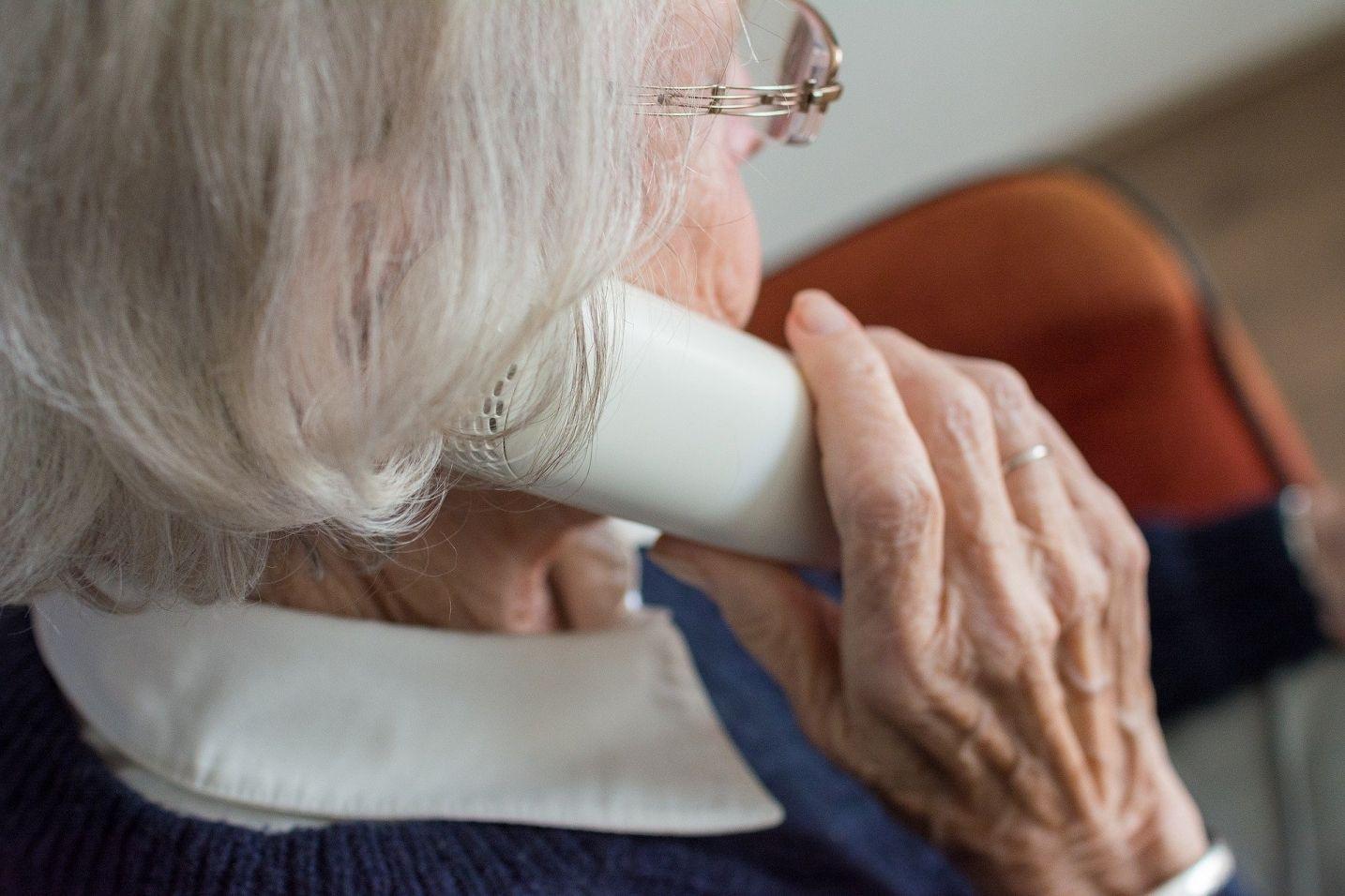zdjęcie przedstawiające profil starszej kobiety starsza kobietę rozmawiającą przez telefon stacjonarny