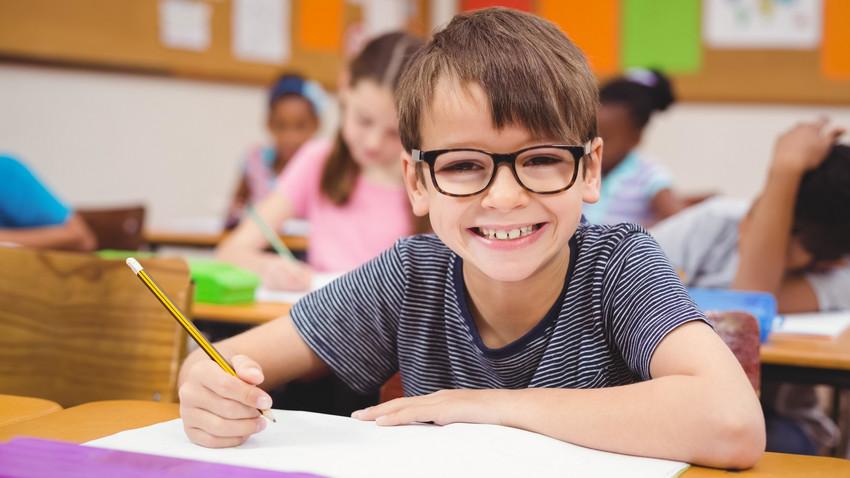 Zdjęcie przedstawiające uśmiechniętego chłopca w ławce szkolnej podczas lekcji piszącego ołówkiem w zeszycie