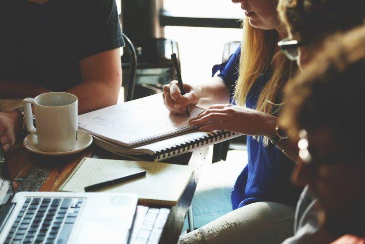 Zdjęcie przedstawiające grupę ludzi przy biurku oraz kobietę robiącą notatki
