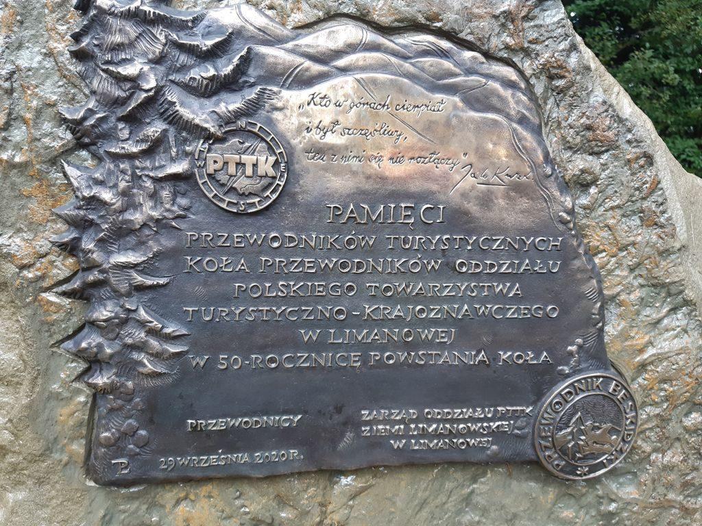 Pamiątkowa tablica umieszczona na kamieniu.