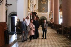 Członkowie komisji kultury powiatu limanowskiego(cztery osoby) stoją w bazylice limanowskiej i patrzą w górę. Towarzyszy im ksiązd proboszcz  Wiesław Piotrowski.