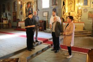 Członkowie komisji kultury powiatu limanowskiego(cztery osoby) stoją przed główyn ołtarzem w kościele Świętego Szymona i Judy Tadeusza Apostołów w Dobrej. Towarzyszy im ksiązd proboszcz  Wojciech Sroka.