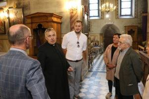 Członkowie komisji kultury powiatu limanowskiego stoją wkościele  Świętego Michała Archanioła w Ujanowicach. Słuchają wypowiedzi księdza proboszcza Wiesława Dzięgiel.
