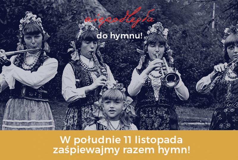 Grafika informująca o wydarzeniu - Niepodległa do hymnu. 4 dziewczynki w regionalnych strojach grające na instrumentach : klarnet, flet, skrzypce i trąbka. Jedna mała dziewczynka w regionalnym stroju stoi przed większymi koleżankami. Na dole biały napis: W południe 11 listopada zaśpiewajmy razem hymn! na zółtym tle.