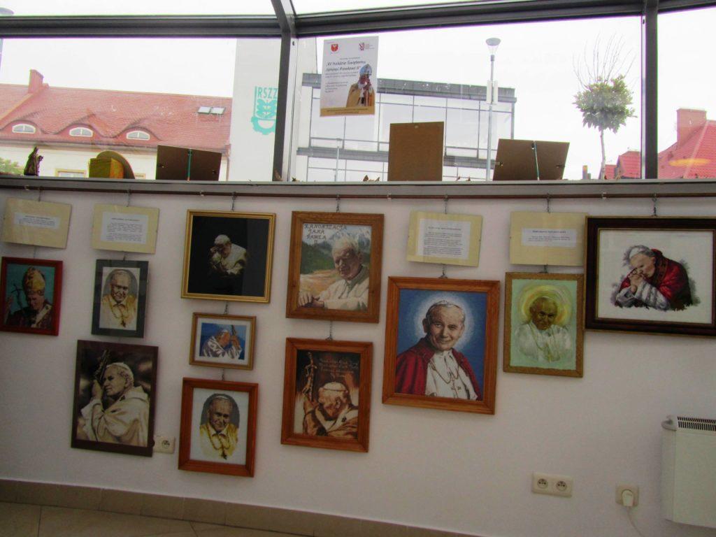 Zdjęcie przedstawiające wiszące obrazy na wystawie w Powiatowym Centrum Informacji Turystycznej