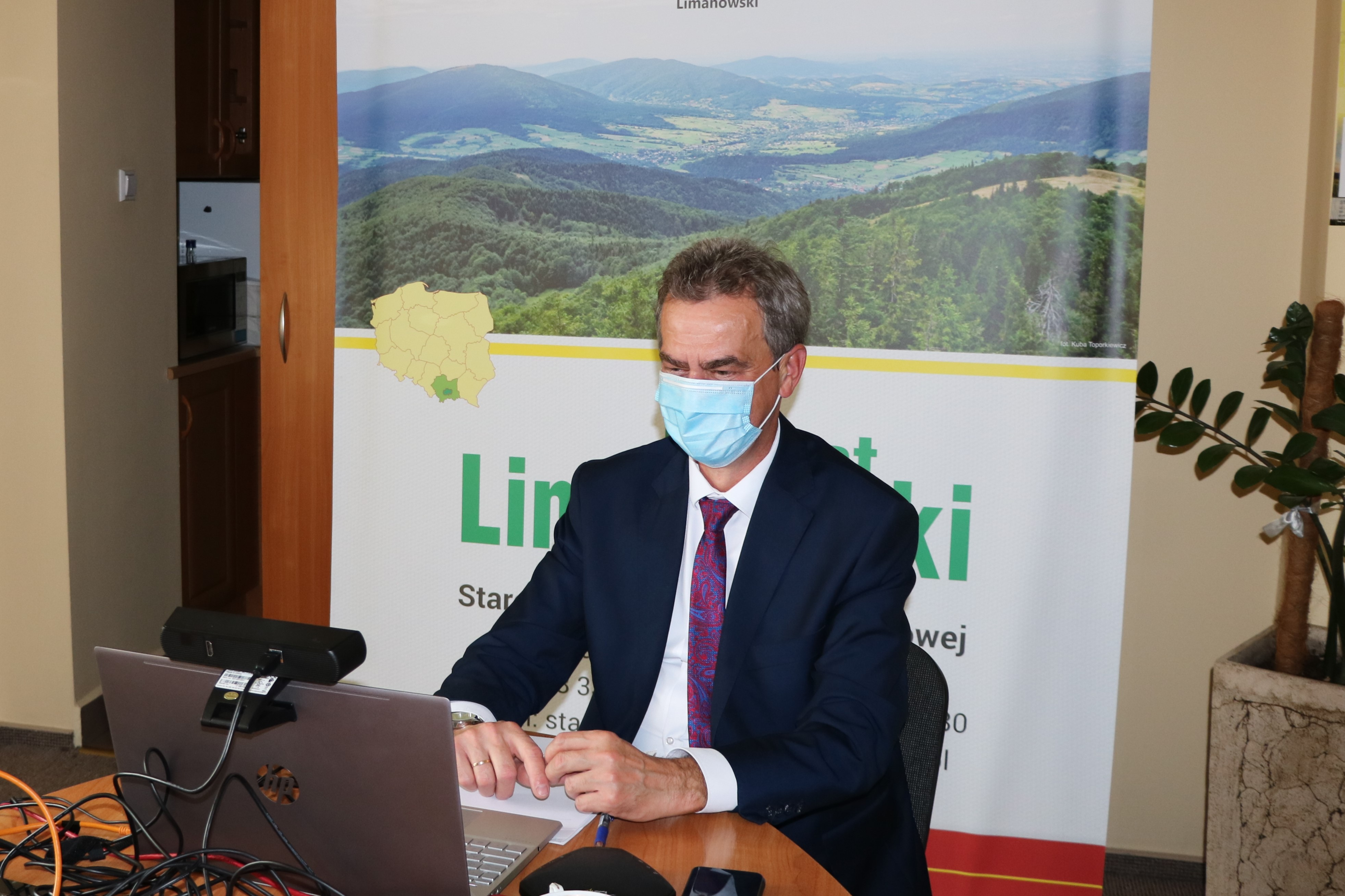 Starosta Limanowski siedzący przed laptoem w sali zarządu podczas konwentu przerowadzanego online.