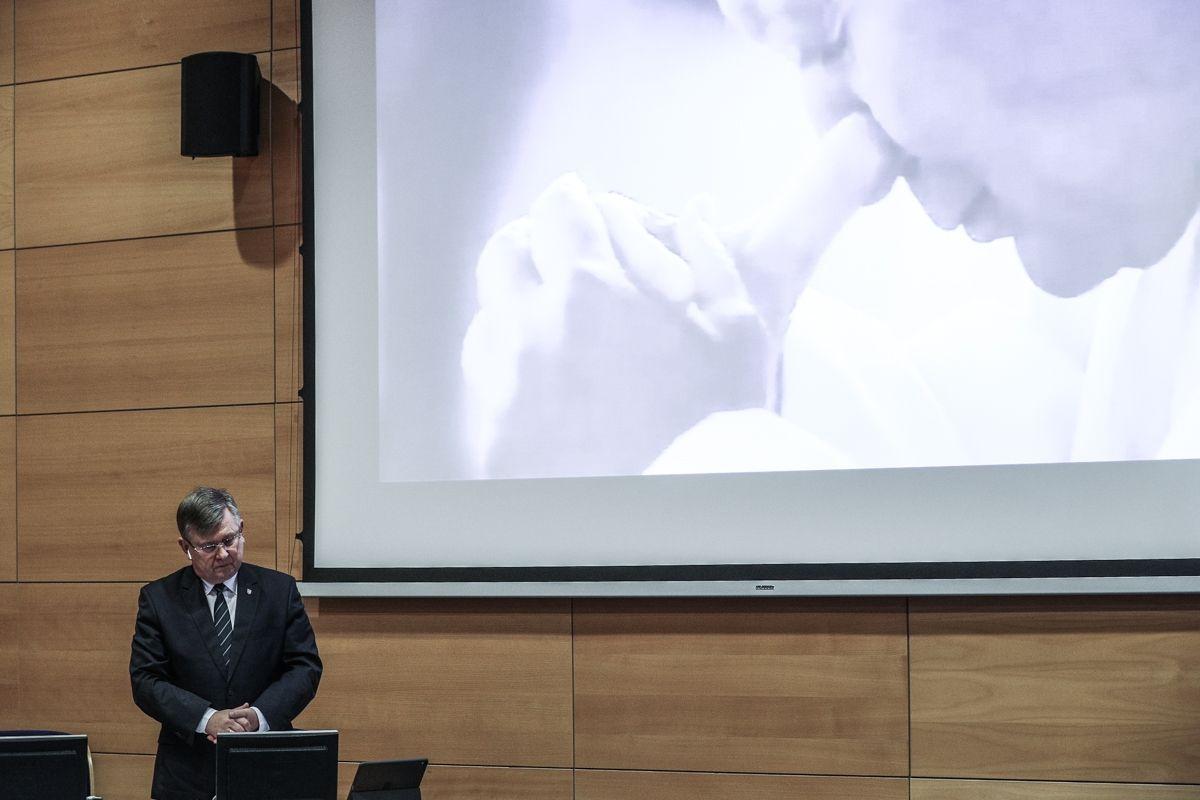 Zdjęcie z obrad sejmiku. Na dużym ekranie (rzutniku) wyświetlona twarz moglącego się papieża. Na mównicy stoi marszałek owjewództwa Witold Kozłowski
