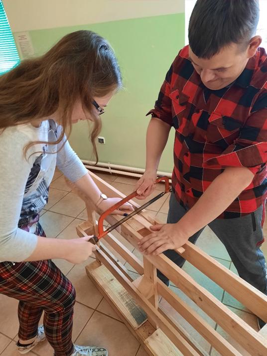 Dwie osoby - dziewczyka i chłopiec podczas przecinania drewnianej palety piłą ręczną.