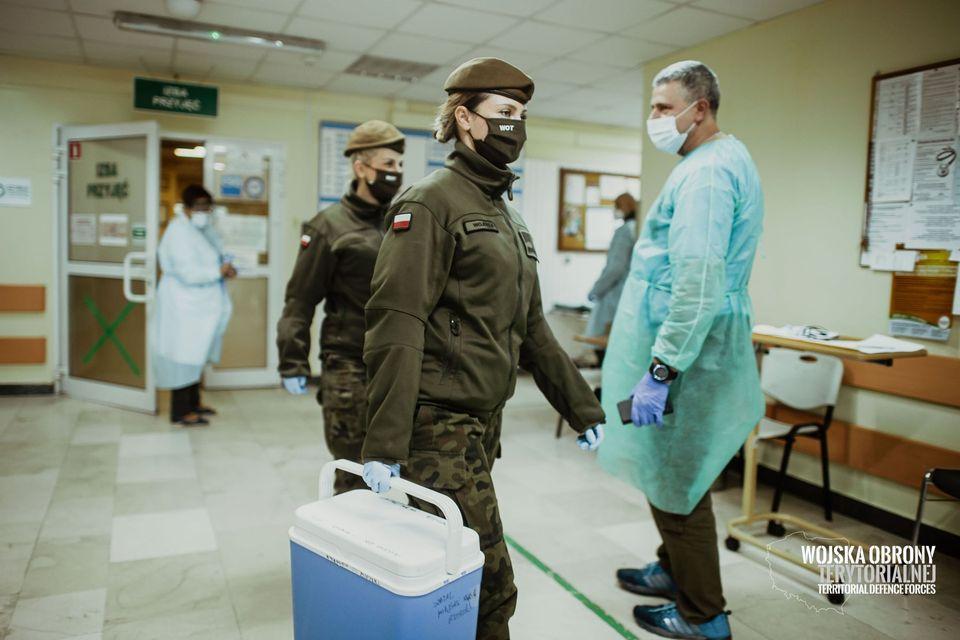 Dwóch żołnierzy na oddziale szpitalnym obok lekarza. Przechodzą przenosząc