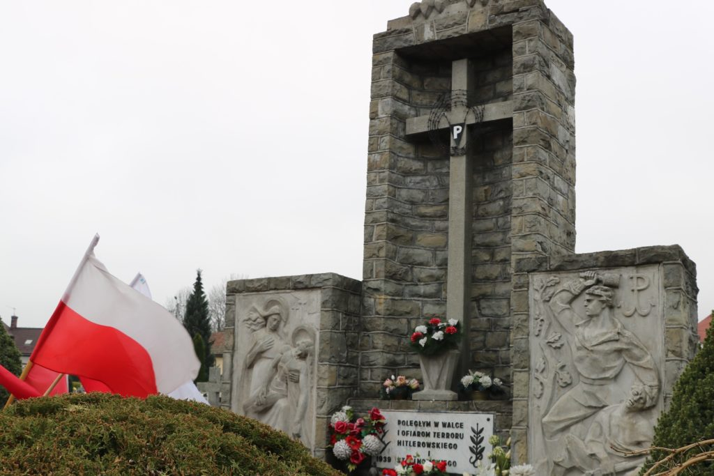 Zdjęcie zlokalizowanego na cmentarzu parafialnym w Mszanie Dolnej,pomnik ofiar II wojny światowej z białoczerwonymi flagami.