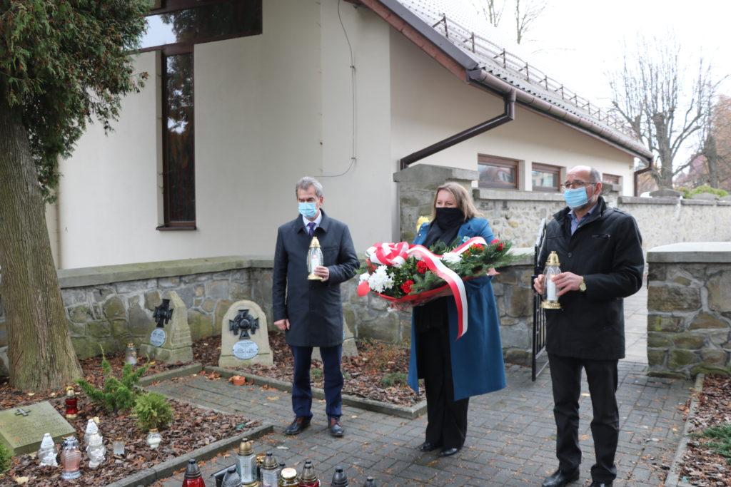 Starosta Limanowski i członek zarządu limanowksiego na cmenatrzu trzymają w rękach znicze. W śródku stoi przewodnicząca rady trzymająca wiązankę patriotyczną.