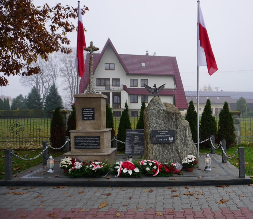Święto Niepodległości w Kamienicy. Pomnik Grunwaldzki i obelisk z legionowym orłem ze złożymi kwiatami. po bokach zawieszone flagi biało czerwone.