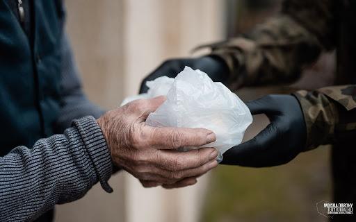 ręcę starszej osoby i żołnierza który przekazuje pakunek.