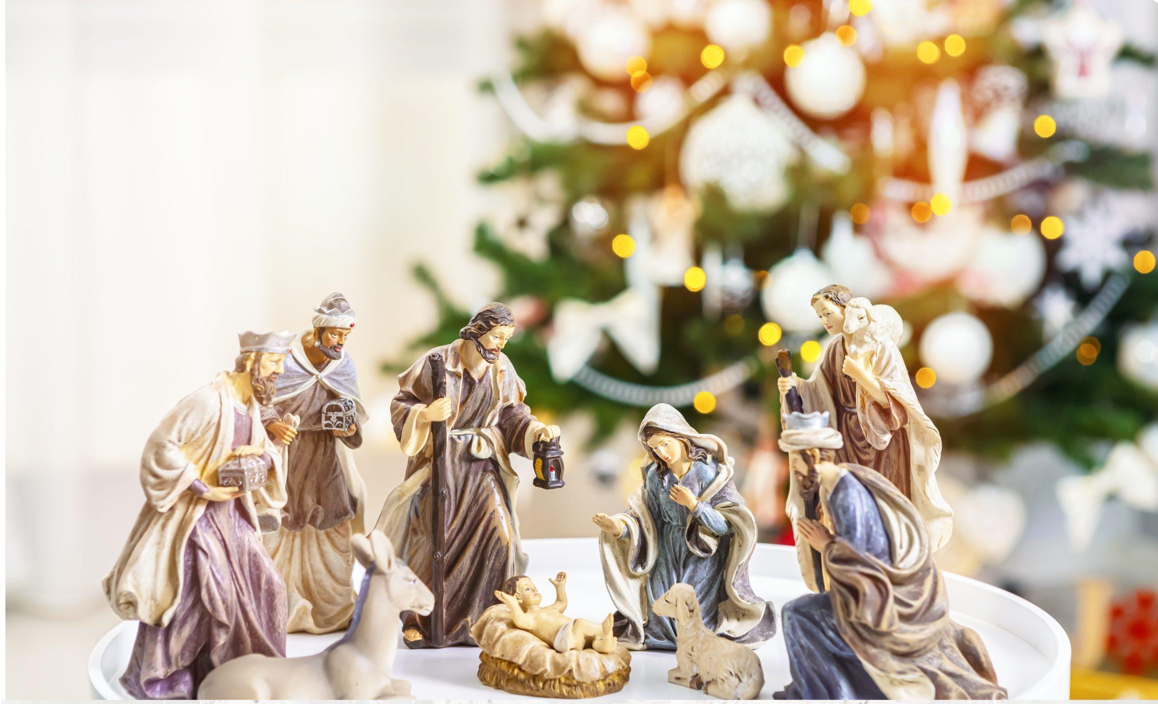 grafika - figurki z szopki bożonarodzeniowej na rozmazanym tle choinki