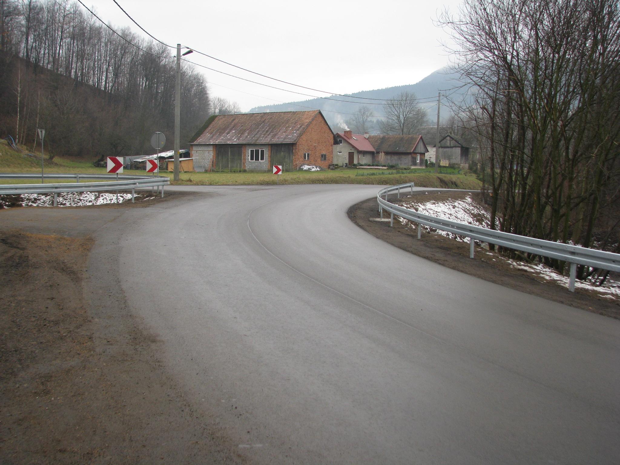 Widok na nową asfaltową poszerzoną jezdnię wraz z poszerzeniem na łukudrogi i poboczem