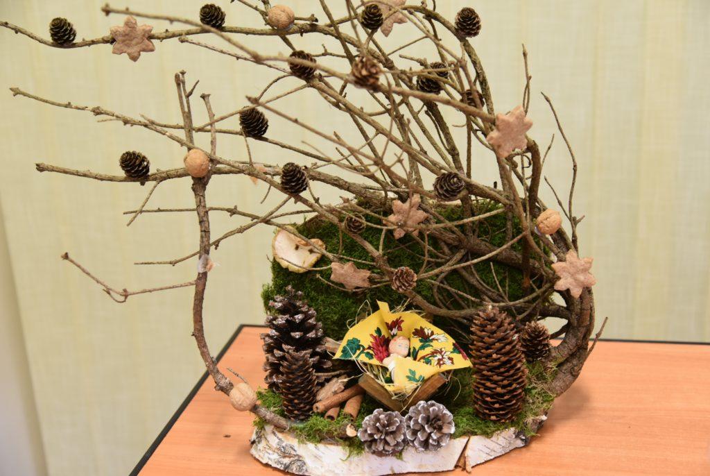 eko szopka z gałęzi, szyszek i mchu. Na środku figura jezuska w złóbku na zołtej folkowej tkaninie.