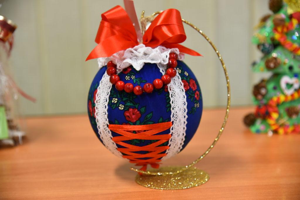 Zdjęcie wygranej pracy w konkursie- bombka laszka. Bombka z granatowego folkowego materiału z biała koronką, czerwoną wstazką i koralami.
