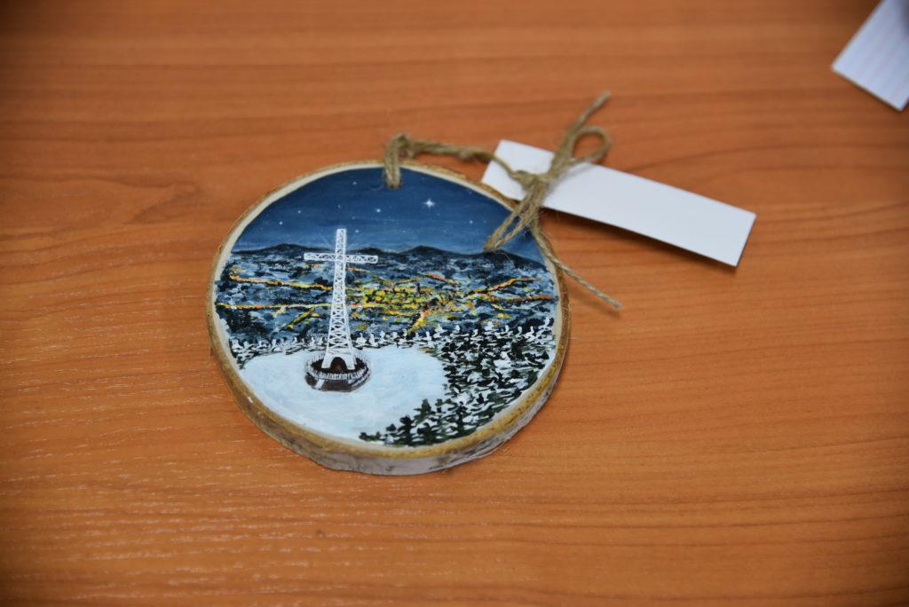 Wyróżniona praca. Drewniana zawieszka z malowanym krzyżem milenijnym i widok nocą na limanową z lotu ptaka.