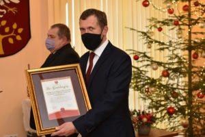 Nagrodozny pozuje z otrzymanym listem gratulacyjnym