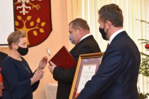 Wicestarosta Agata Zięba wręcza piny z herbem powiatu limnaowksiego przedstawicielom chóru.