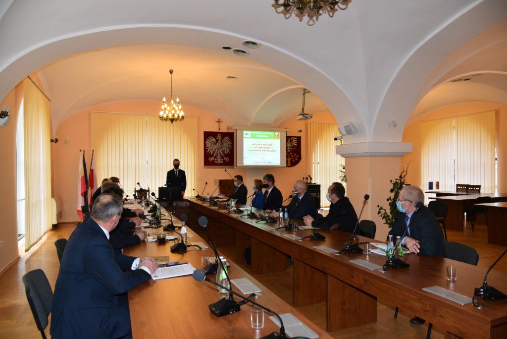 Uczestnicy spotkania siedzą przy stole w sali konferencyjnej. Starosta Limanowski przemawia na stojąco przy stole prezydialnym.