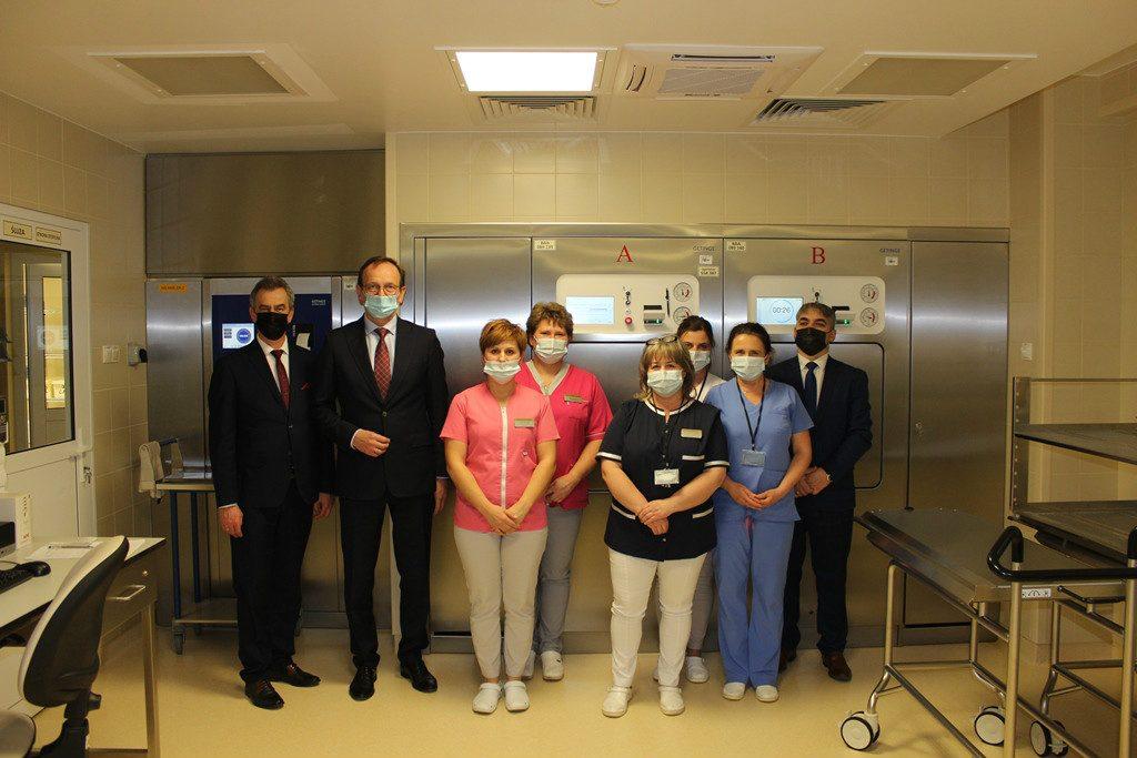 Minister Edward Siarka wraz ze starostą limanowski, dyrektorem spzitala i pielęgniarkami stoją przy sterylizatorze parowy w Centralnej Sterylizatorni Szpitala.