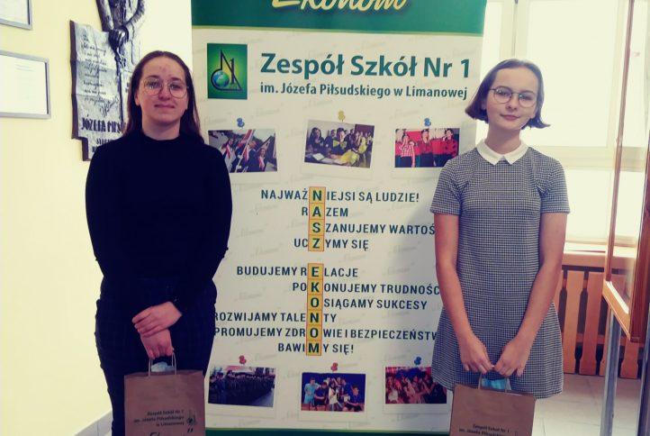 dwie dziewczyny stojące na tle rollupu szkoły trzymają torby z nagrodami.