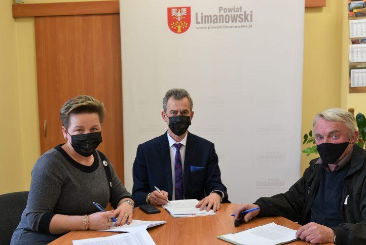 Starosta Limanowski w towarzystwie wicestarosty i przewoźnika podpisują umowę. Siedzą przy stole w tle baner powiatu limanowskiego.