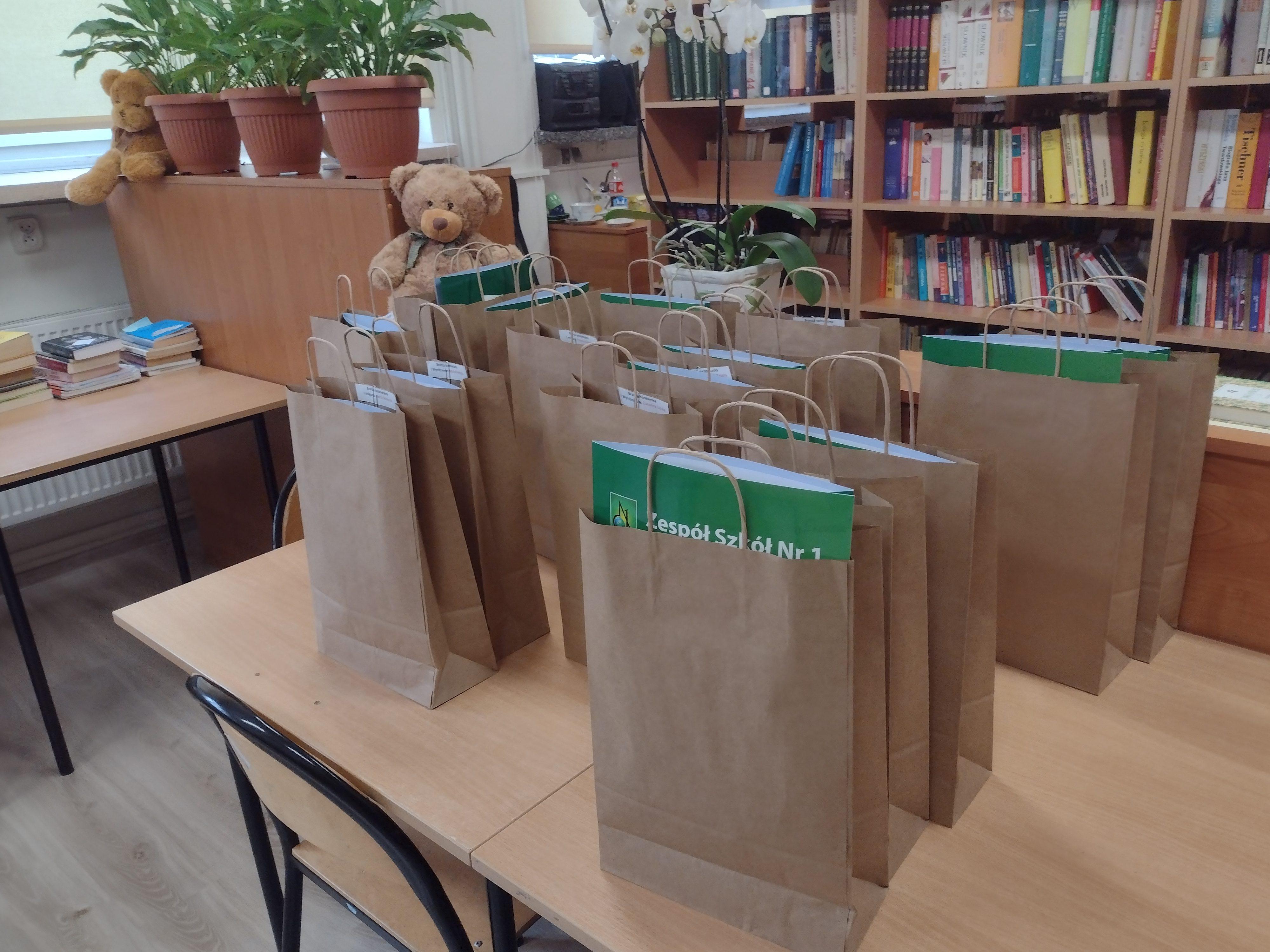 Szare torby z upominkami położone na ławce w klasie