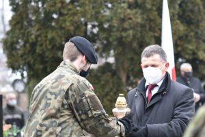 Wójt Gminy Niedźwiedź Rafał Rusnak podczas przekazania znicza na ręce strzelca do zlożenia na gorbie poległych żołnierzy.